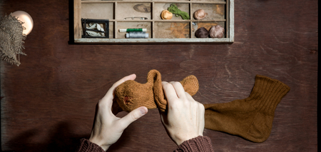 darning needle: Human hands darning sock over desk with handmade accessories. Top view. Stock Photo
