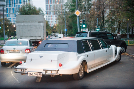 front bumper: Moscow, Russia - October 2, 2015: Wedding white limo drives out of the parking lot.
