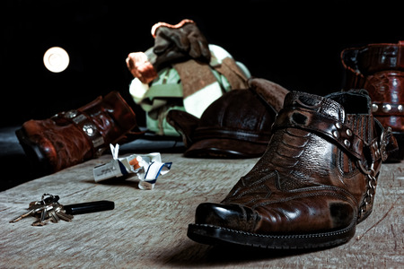 warm things: Carelessly thrown on the wooden floor male accessories: cowboy shoes, bag and others.