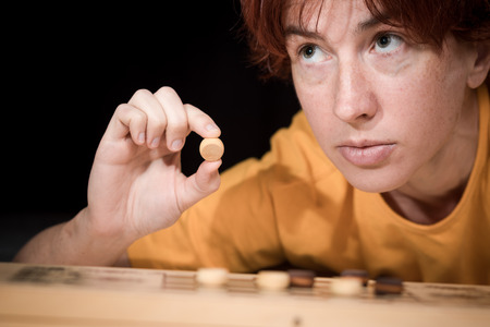 checker board: Ordinary woman leaning over a checker board with the set pieces.