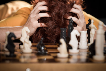 ordinary woman: Ordinary woman  grabbing her head over a chessboard with the set pieces.