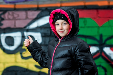 hooded vest: Young girl in hooded vest thumbing to the graffiti on the wall. Stock Photo