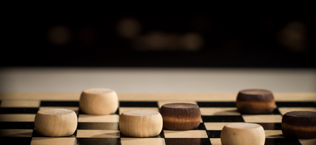 etude: Closeup of wooden checkers on the board.