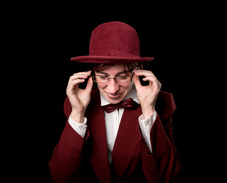 wry: Strange person in a suit and bowler  adjusting her glasses with a smile. Stock Photo