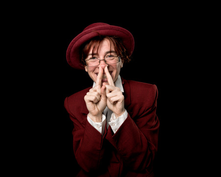 wry: Strange person in a suit and bowler laughing, holding two fingers in the nose.