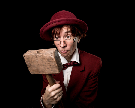 astonishment: Strange person in a suit and bowler  looking at wooden hammer in astonishment.
