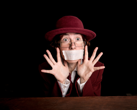 exaggerated: Strange person in a suit and bowler with a taped mouth and pleading eyes.
