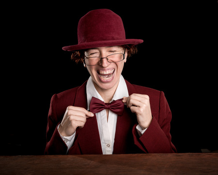 exaggerated: Strange person in a suit and bowler straightening bow tie laughing. Stock Photo