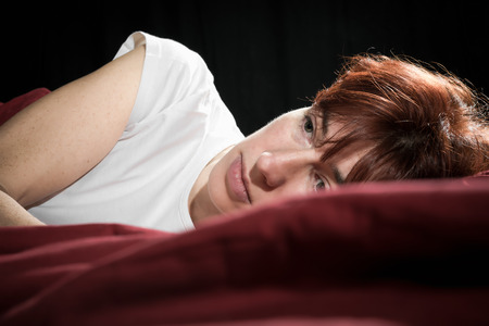 sadly: Woman lying in a bed looking sadly.