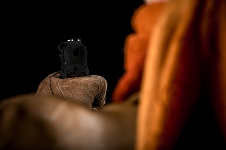 shot from behind: Shot from behind the shoulder of the person in the hat and the suede glove aiming a pistol.
