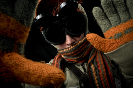 strange: Strange man with paranoid tendencies in goggles, a baseball cap, scarf, gloves and hood on black background.
