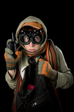 nutty: Strange man with paranoid tendencies in goggles, a baseball cap, scarf, gloves and hood on black background.