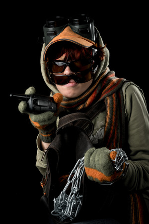 paranoid: Strange man with paranoid tendencies in goggles, a baseball cap, scarf, gloves and hood on black background.