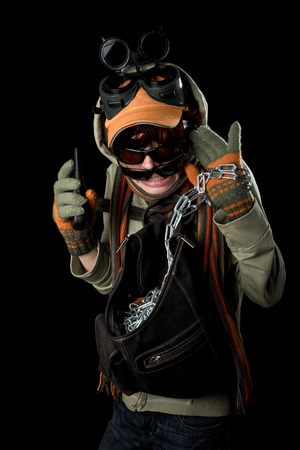 tendencies: Strange man with paranoid tendencies in goggles, a baseball cap, scarf, gloves and hood on black background.