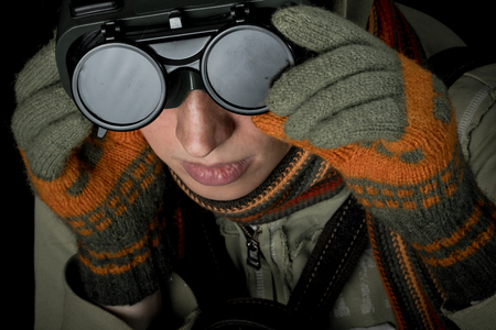 distrustful: Strange man with paranoid tendencies in goggles, a baseball cap, scarf, gloves and hood on black background.