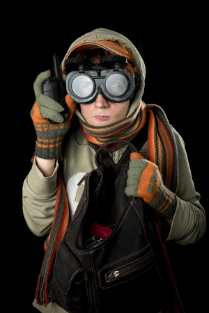 cautious: Strange man with paranoid tendencies in goggles, a baseball cap, scarf, gloves and hood on black background.