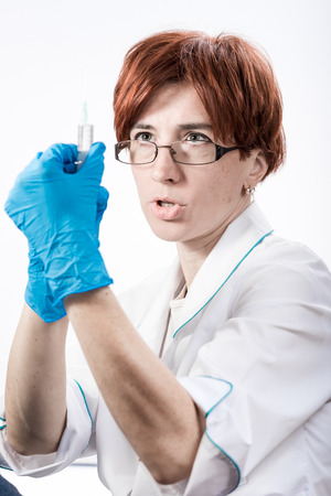 recuperation: Woman in a white uniform blouse and gloves holding a syringe.
