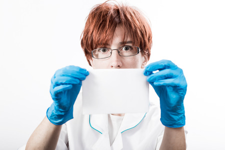 women s health: Woman in a white uniform blouse and gloves holding blank sheet of paper. Stock Photo