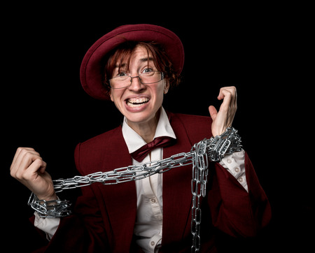 exaggerated: Strange person in a suit and bowler  trying to free herself from the chain on her hands.
