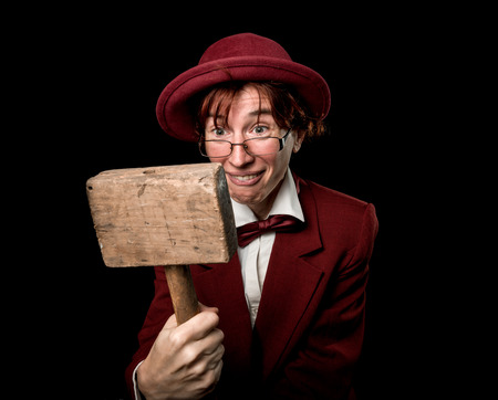 wry: Strange person in a suit and bowler  looking at wooden hammer in astonishment.