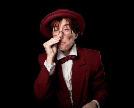 exaggerated: Strange person in a suit and bowler sniffing raising her hand to her nose.
