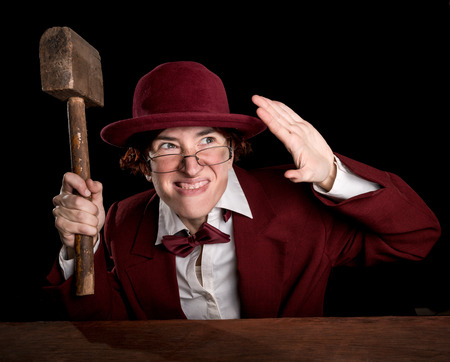 exaggerated: Strange person in a suit and bowler holding wooden hammer and shut her face by hand.