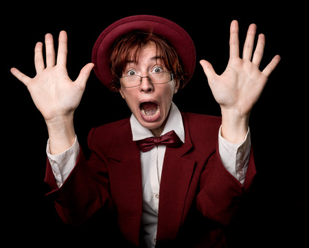 bowler: Strange person in a suit and bowler with her hands raised and a frightened face. Stock Photo