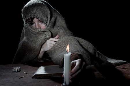 beggary: Enclosed nun sitting above a book in the dark cell. Stock Photo