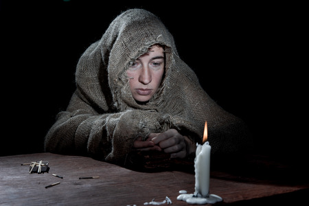 meanness: Extremely poor woman counting change in the dark room.