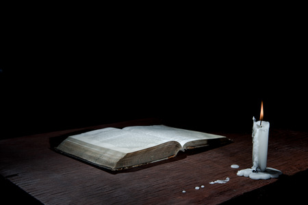 beggary: Candle  and book on table in empty dark room.
