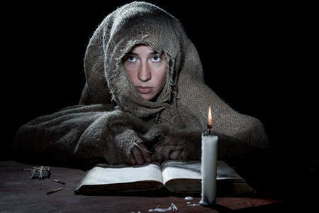 penitence: Extremely poor woman sitting above a book in the dark room. Stock Photo