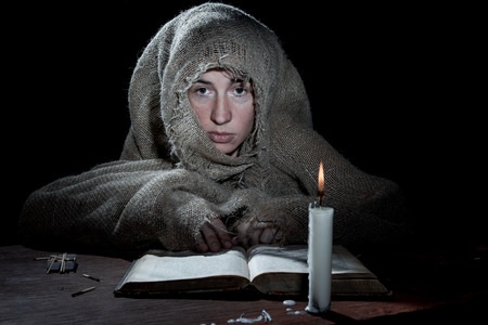 beggary: Extremely poor woman sitting above a book in the dark room. Stock Photo