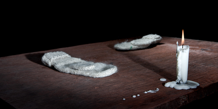 obscurity: Candle and mittens on table in empty dark room.