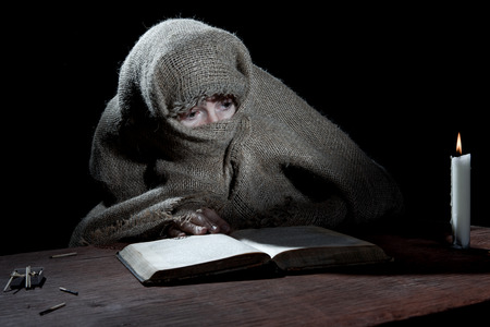 penitence: Enclosed nun sitting above a book in the dark cell. Stock Photo