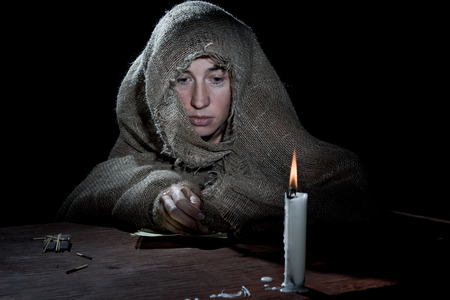 beggary: Poor nun sitting above a letter in the dark room.