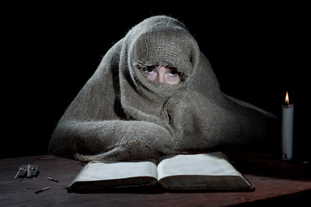 penury: Enclosed nun sitting above a book in the dark cell. Stock Photo