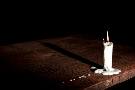 futility: Candle on table in empty dark room.