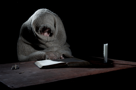 recluse: Enclosed nun sitting above a book in the dark cell. Stock Photo
