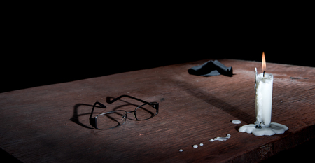 blackness: Candle, eye glasses and napkin on table in empty dark room. Stock Photo