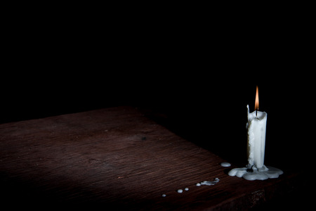 beggary: Candle on table in empty dark room.