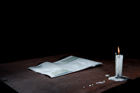 destitute: Candle and paper on table in empty dark room. Stock Photo