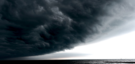 leaden: Huge leaden cloud overcasting the sky above the sea surface. Storm is coming.