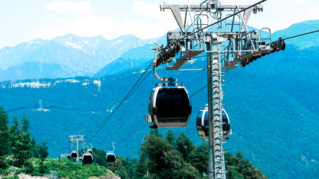spaciousness: Cable cabins lifting to the mountains at the ski resort in the summer.
