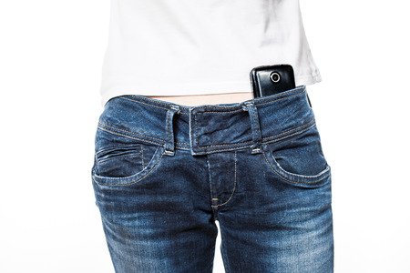 body parts cell phone: Female hips in blue jeans with cell phone in the belt.