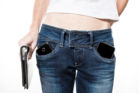 body parts cell phone: Female hips in blue jeans with cell phones in pockets and tablet in hand.