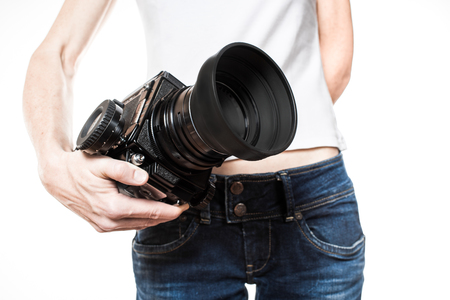 medium body: Female hips in blue jeans with medium-format camera in a hand. Stock Photo