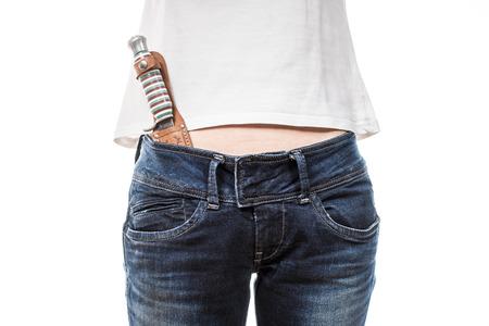 schwertscheide: Female hips in blue jeans with hunting knife in pocket. Lizenzfreie Bilder