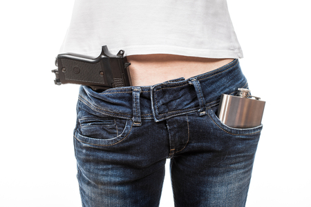 drunkenness: Female hips in blue jeans with air gun and silver flask in front pockets. Stock Photo