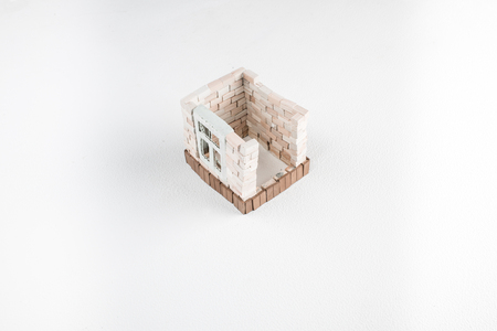 continued: Construction of toy brick house in progress. White background. Top perspective view.