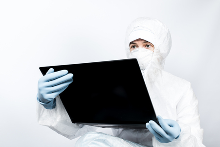 infective: Female professional in hooded suit for bio-hazard protection on white background. Stock Photo